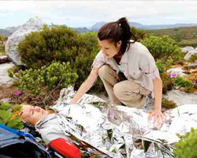 Outdoor first aid showing emergency foil blanket